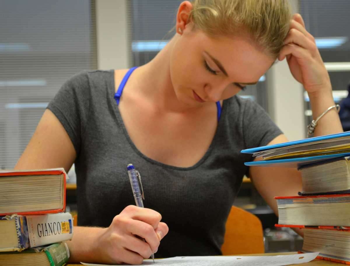 Kaitlyn Needler ('18) is surrounded by piles of work and piles of homework as she works during her off block in the RV library.