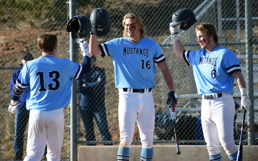 Seniors (from left) Otto Jones, AJ Jergensen, and Trey Adams celebrate a home run for the team.