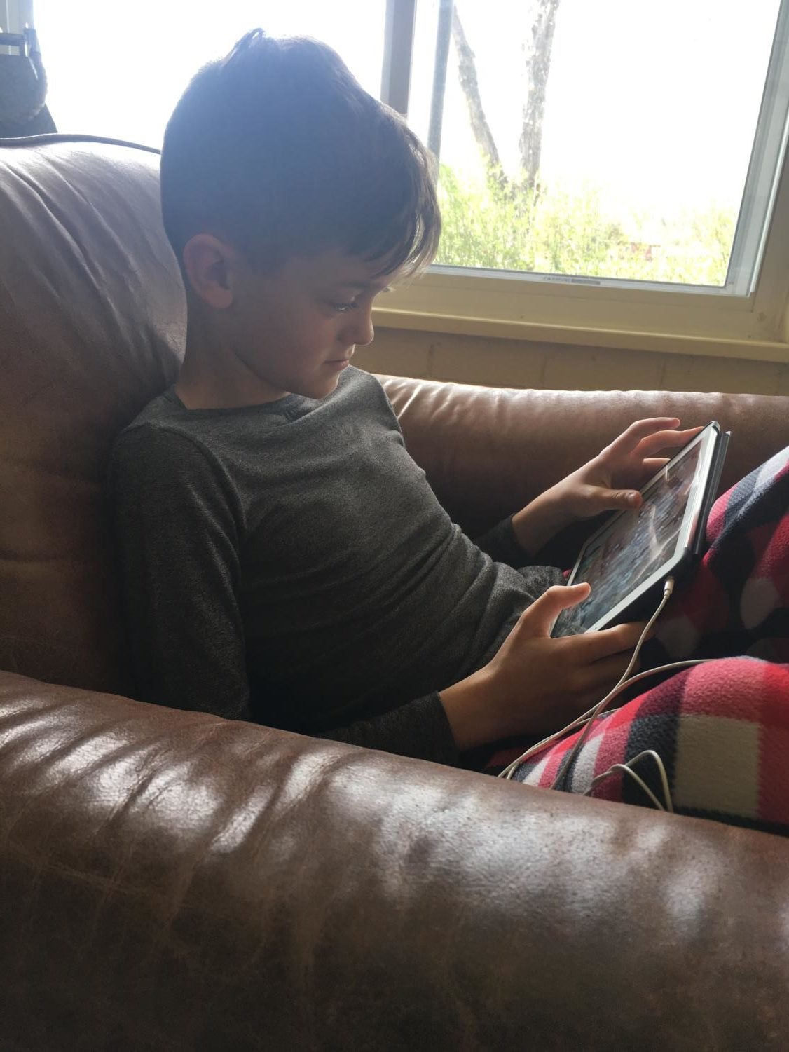 Gage Clymer playing a game on his iPad. (photo by Jody Clymer)